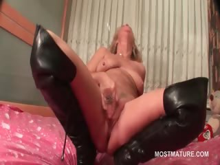 aged in leather boots doing herself in sofa